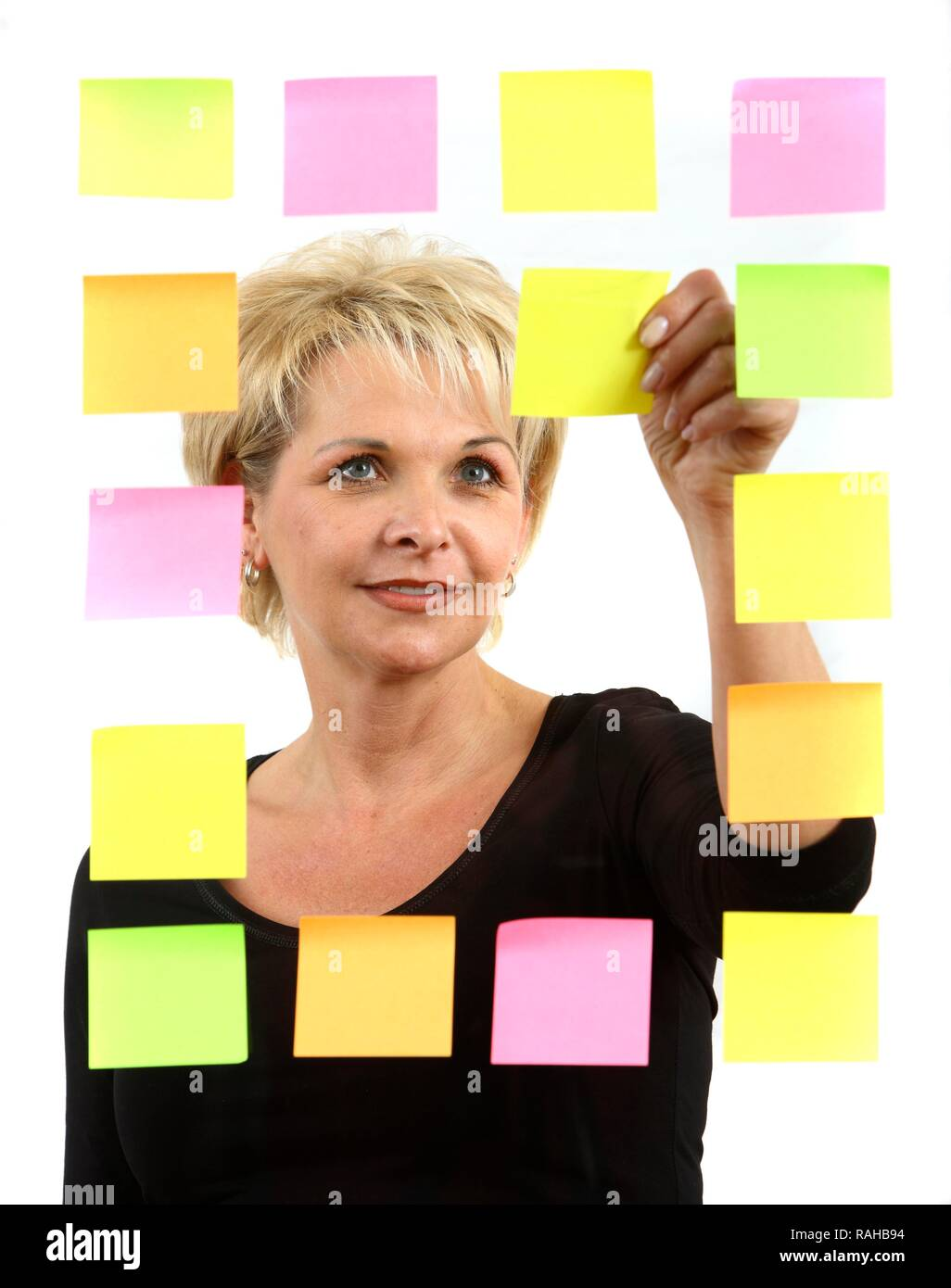 Woman sticking PostIt sticky notes to a sheet of glass - Stock Image