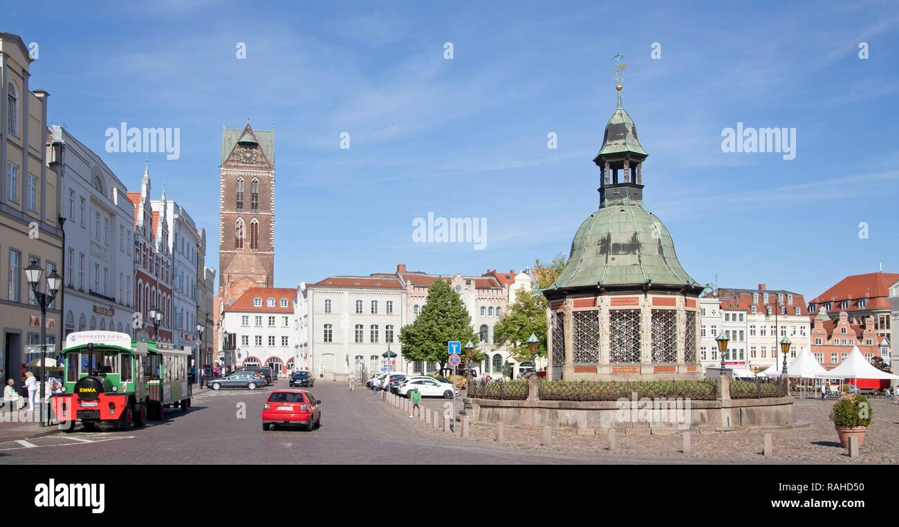 Market square or market place with the Wasserkunst fountain and the steeple of St. Mary's church, Wismar - Stock Image