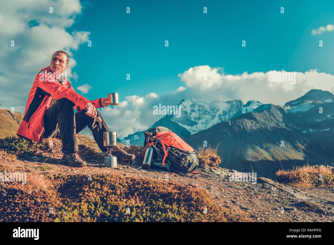 Hot Drink on a Trail. Caucasian Backpacker in His 30s Taking Short Break and Enjoying Warm Tea. - Stock Image