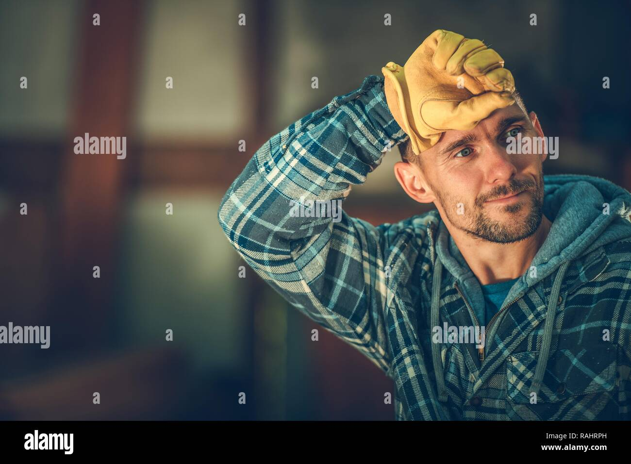 Tired by Happy Caucasian Worker in His 30s. Construction Industry. Stock Photo