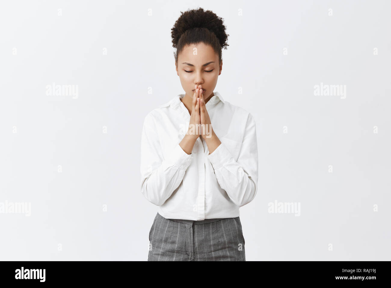 Time to pray and talk with mighty god. Relaxed and focused good-looking dark-skinned female entrepreneur calming down while holding palms together, praying or hoping, being believer in miracles - Stock Image