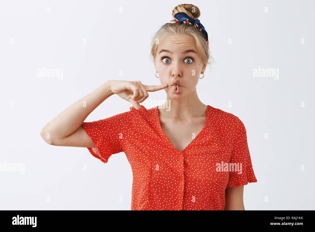 Funny expressive attractive blonde female student in vintage red polka-dot blouse and headband folding mouth in fish lips and poking cheek standing with childish expresion over grey wall - Stock Image