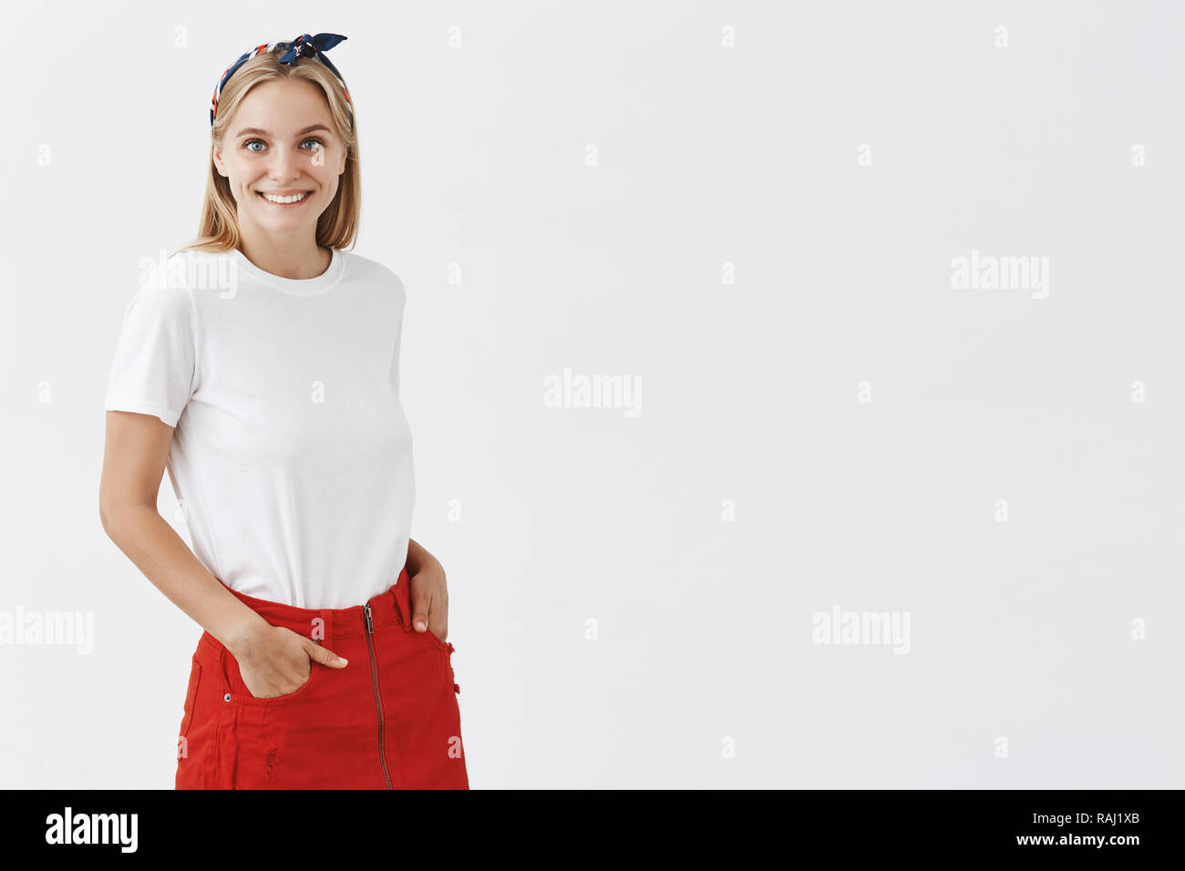 Girl can brigthen up every fashion event. Portrait of charming happy and carefree stylish blonde european female in red skirt and headband, smiling cute and holding hands in pockets - Stock Image
