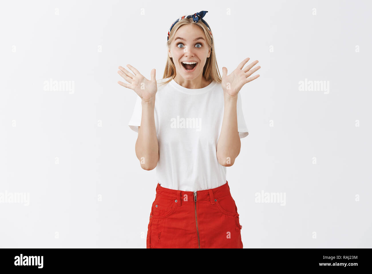 Girl being surprised by friend coming to work with gift. Attractive happy and emotive good-looking European female in headband and red skirts, gasping with broad smile, gesturing with raised palms - Stock Image