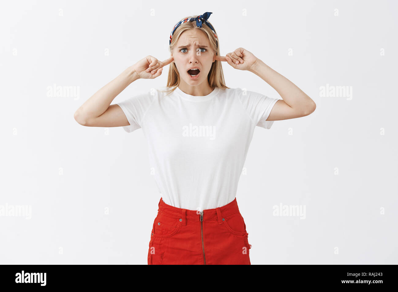 Turn off this rock and turn my songs. Displeased bothered attractive caucasian sister with blond hair in trendy outfit, frowning and gasping, plugging index fingers in ears. being annoyed with noise - Stock Image