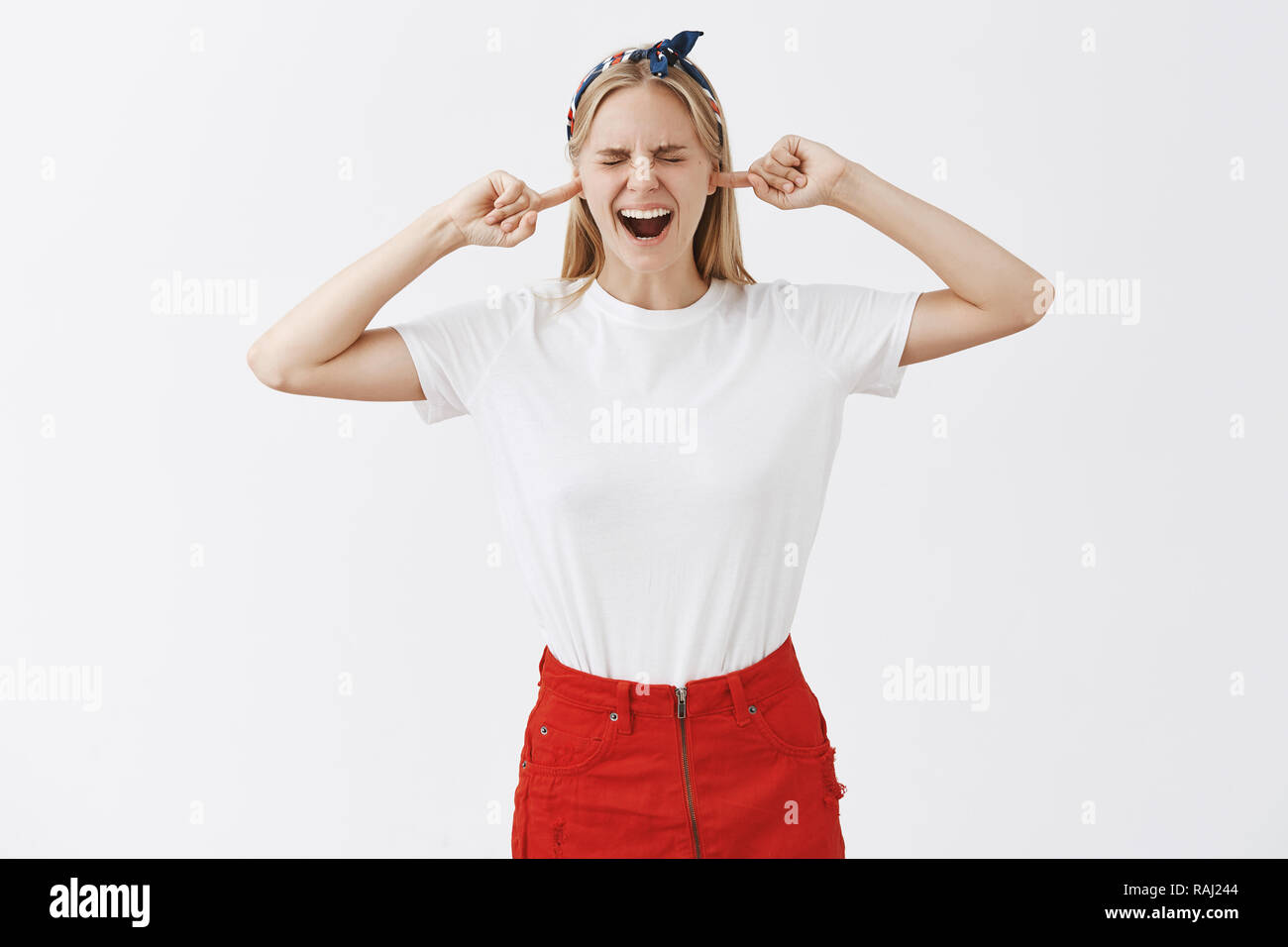 Studio shot of displeased uncomfortable good-looking blond girl in headband and red skirt, screaming with closed eyes and earplugs made from inde fingers hearing loud disturbing sound - Stock Image