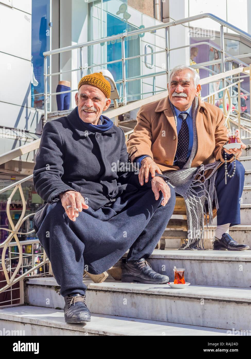 Istanbul, Turkey, February 24, 2015: Two elderly Turkish men seated on some steps, drinking Turkish tea. Stock Photo
