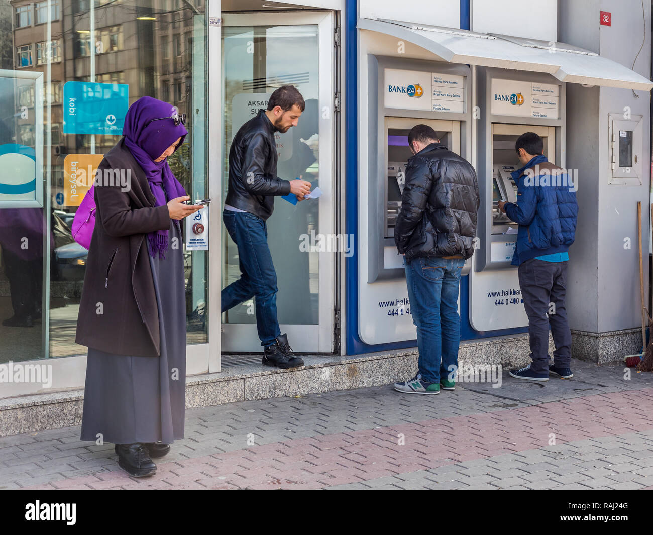 Istanbul, Turkey, February 24, 2015: Four Turkish people in a street, looking down, absorbed in their own activities. - Stock Image