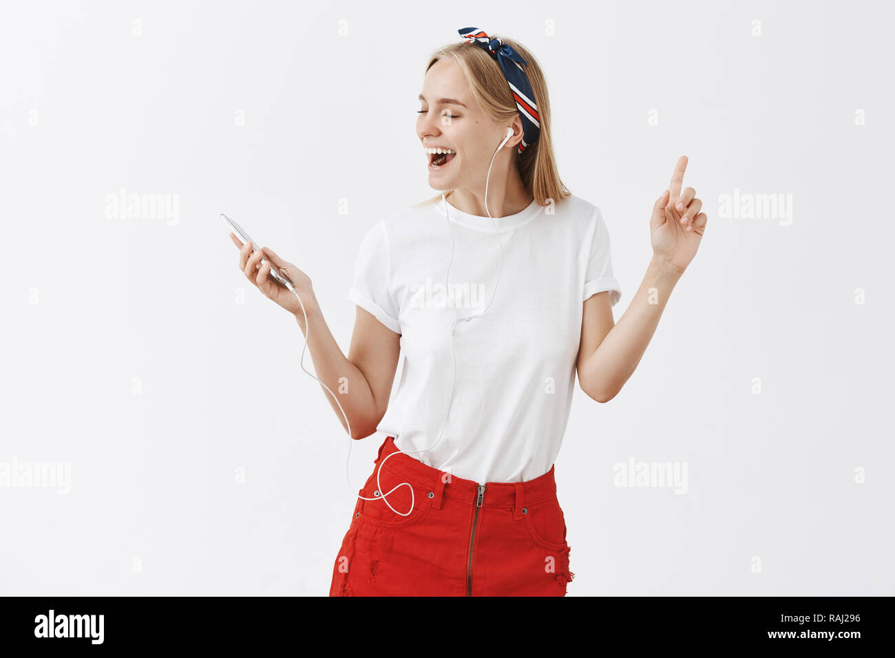 Portrait of charming carefree blonde female in stylish outfit dancing with raised hands turning left and singing along favorite songs, listening music in earphones, holding smartphone in hand - Stock Image