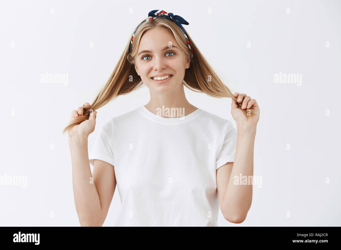Happy attractive and emotive blond woman in headband and white t-shirt pulling hair strands with hands and smiling joyfully looking in mirror, thinking about visiting hairdresser and change haircut - Stock Image