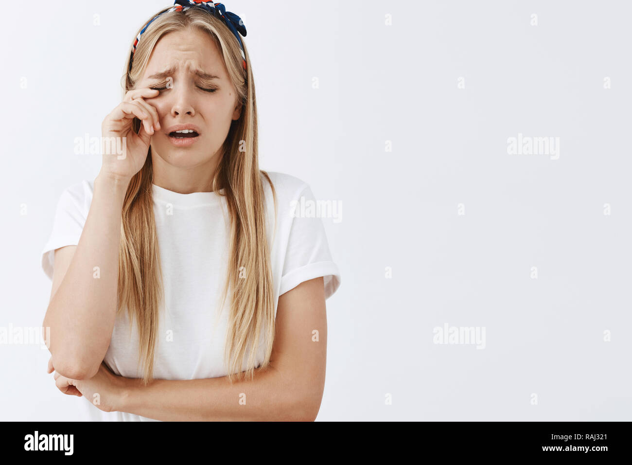 Crying her heart out, he does not worth your tears honey. Sad insecure and timid young girl with blond hair, frowning, whiping teardrop from eye while being upset and unhappy over grey wall - Stock Image