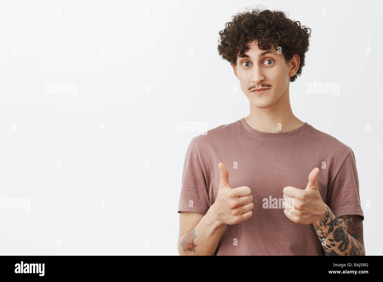 Nice really like it. Surprised and impressed good-looking stylish male friend with moustache and curly hairstyle showing thumbs up raising eyebrows and nodding in approval gesture being supportive - Stock Image