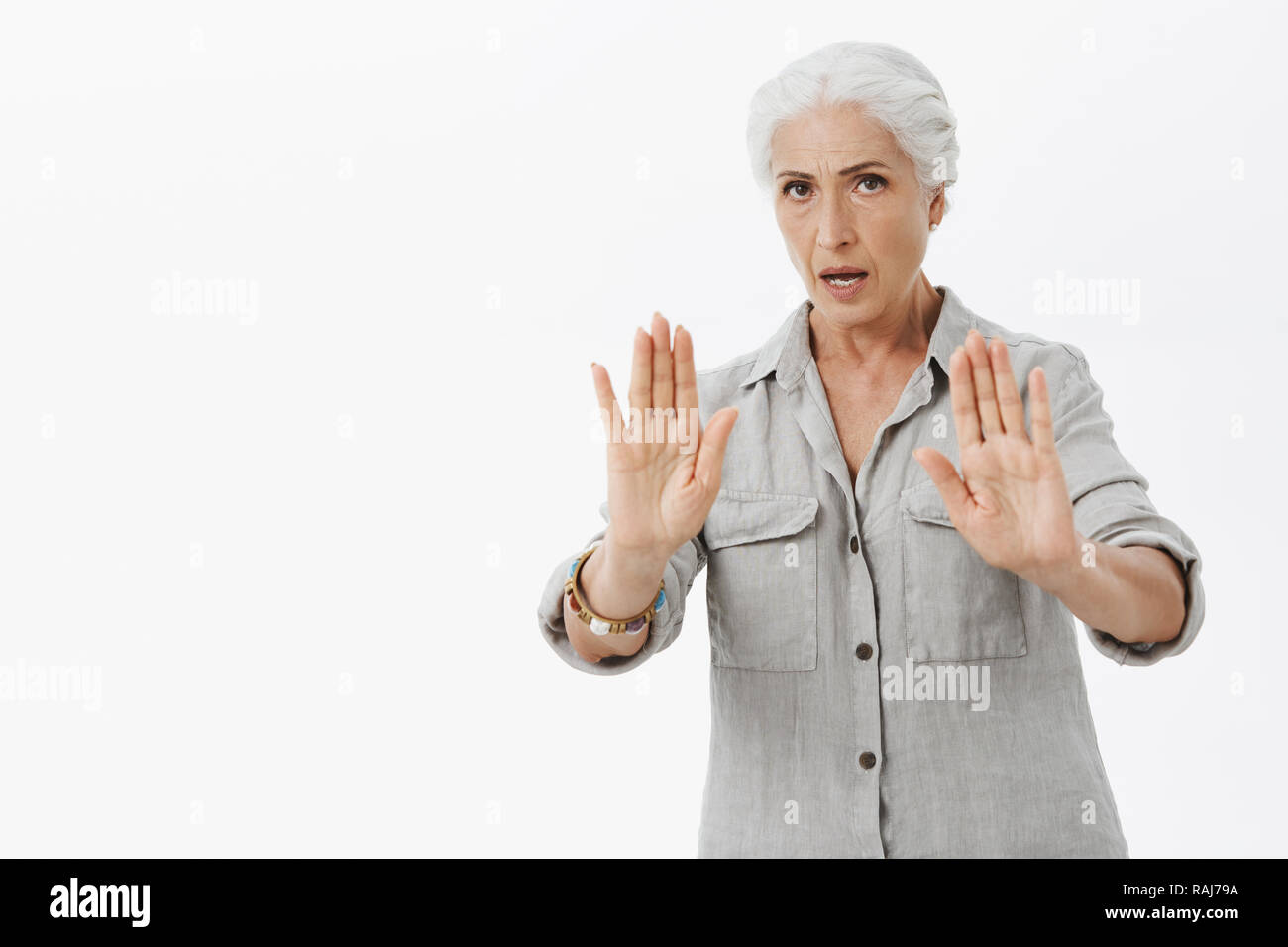 Serious-looking intense and wise elderly mother warn son to calm down raising palms, trying carefully talk to reduce pressure, asking relax and not worry, rejecting something or showing stop gesture - Stock Image