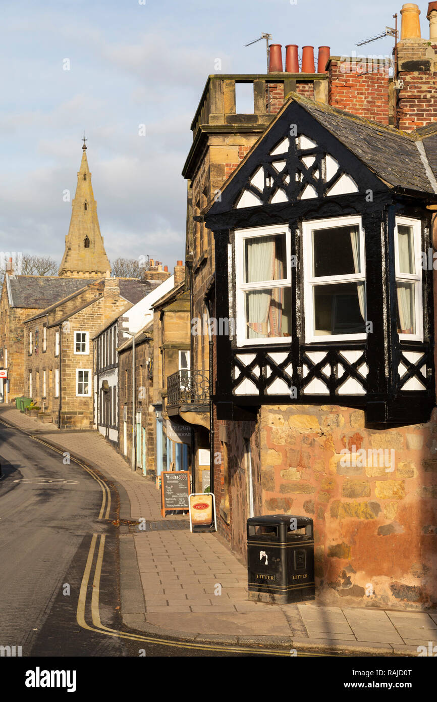 A half-timbered facade at Alnmouth in Northumberland, England. A litter bin stands on the pavement. - Stock Image