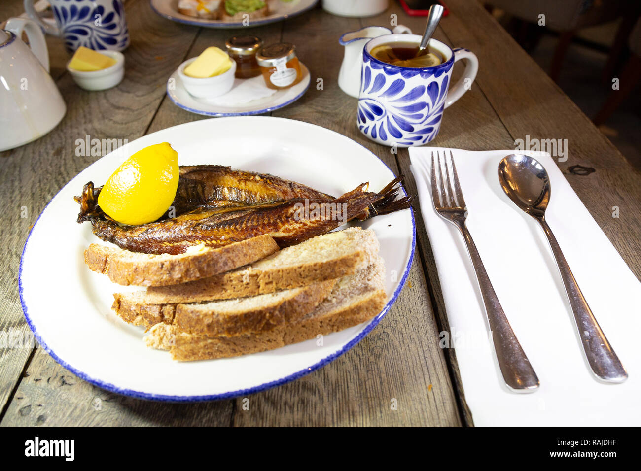 Craster kipper served with toast for breakfast in Northumberland, England. The Northumbrian delicacy is served with Earl Grey tea. - Stock Image