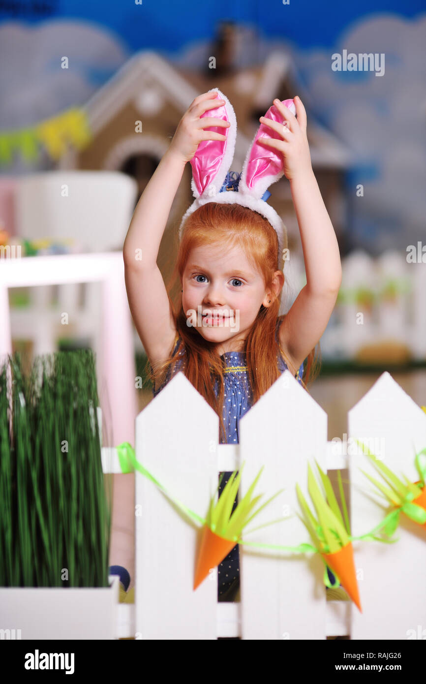 girl with rabbit ears smiling and grimacing against the white fence. Preparation for the celebration of Easter. - Stock Image