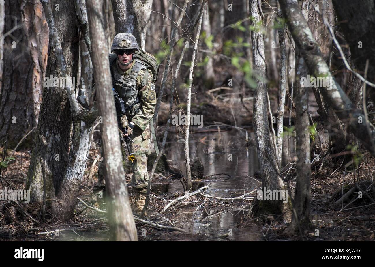 Airman 1st Class Daniel Ross, 822d Base Defense Squadron fireteam member, looks for signs of improvised explosive devices, while simulating patrolling an area outside the wire Feb. 7, 2017, at Moody Air Force Base, Ga. Airmen simulated various missions they would be tasked to complete during a deployment, including being ambushed while out on patrol, gathering intelligence from residents in the local village and raiding buildings. - Stock Image
