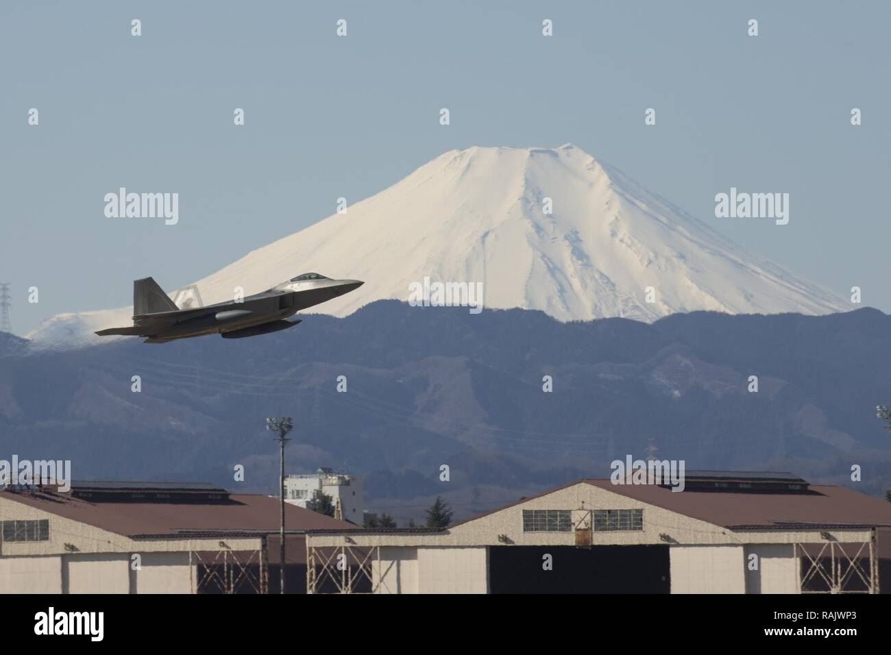A U.S. Air Force F-22 Raptor from the 90th Fighter Squadron at Joint Base Elmendorf-Richardson, takes off at Yokota Air Base, Japan, Feb. 13, 2017. The F-22 Raptors stopped at Yokota AB before traveling on to Royal Australian Air Force Base, Tindal. As the Air Force's Western Pacific airlift hub, Yokota supports transient aircraft as they conduct mission throughout the Indo-Asia Pacific Region. - Stock Image