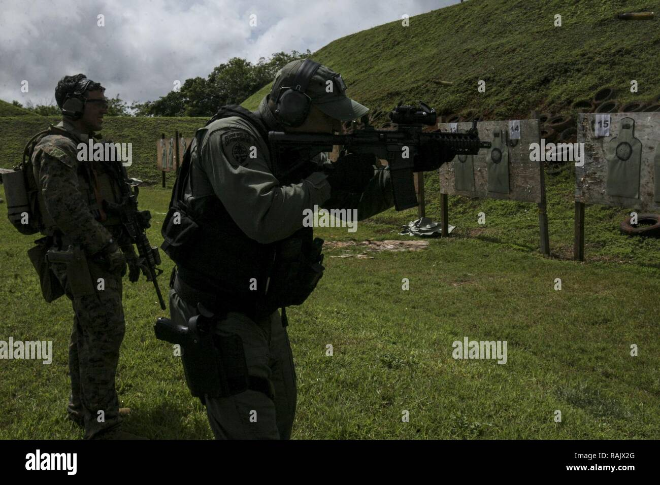 Sgt. Luis Martinez, a reconnaissance Marine, with Maritime Raid Force, 31st Marine Expeditionary Unit, conducts a live-fire range with police officers and SWAT members of the Guam Police Department at Anderson Air Force Base, Guam, Feb. 7, 2017. The MRF Marines trained with the police officers and SWAT team members as a gesture of good will between the two forces.  As the Marine Corps' only continuously forward-deployed unit, the 31st Marine Expeditionary Unit's air-ground-logistics team provides a flexible force, ready to perform a wide range of military operations, from limited combat to hum - Stock Image