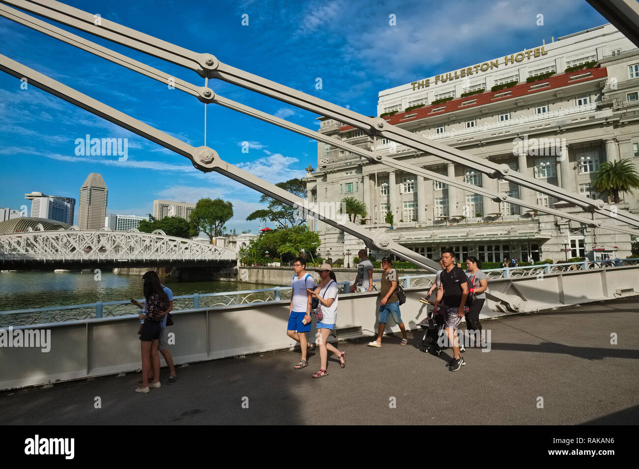 Tourists crossing Cavenagh Bridge spanning the Singapore River, Singapore, in the background Anderson Bridge (l) and Fullerton Hotel (r) - Stock Image
