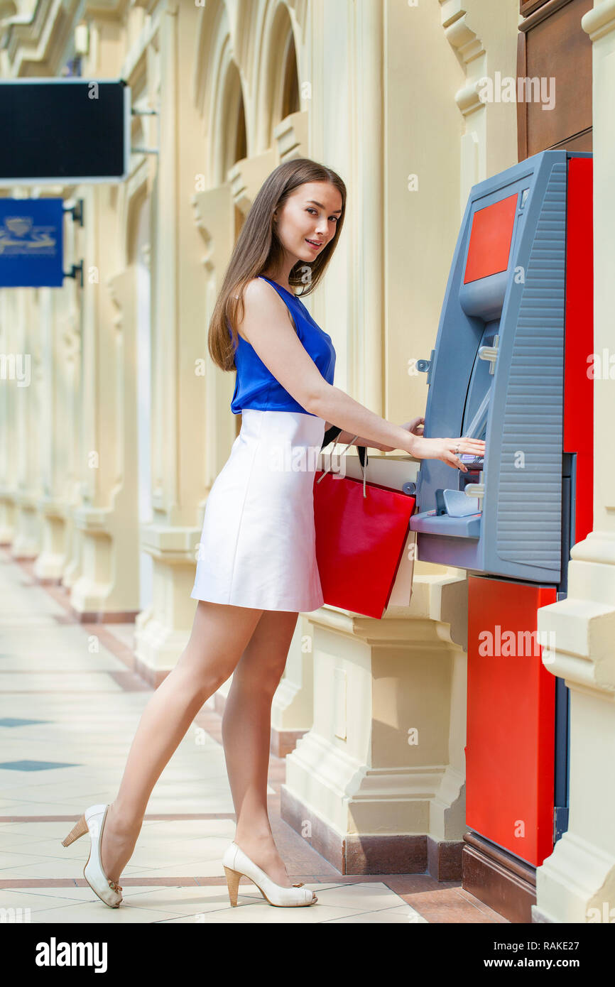 69380d0bec63 Young happy brunette woman withdrawing money from credit card at ATM ...