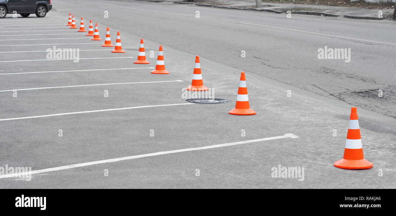 Car parking lot and orange traffic cone. Closed car parking lot with white mark and traffic cone on street used warning sign on road - Stock Image