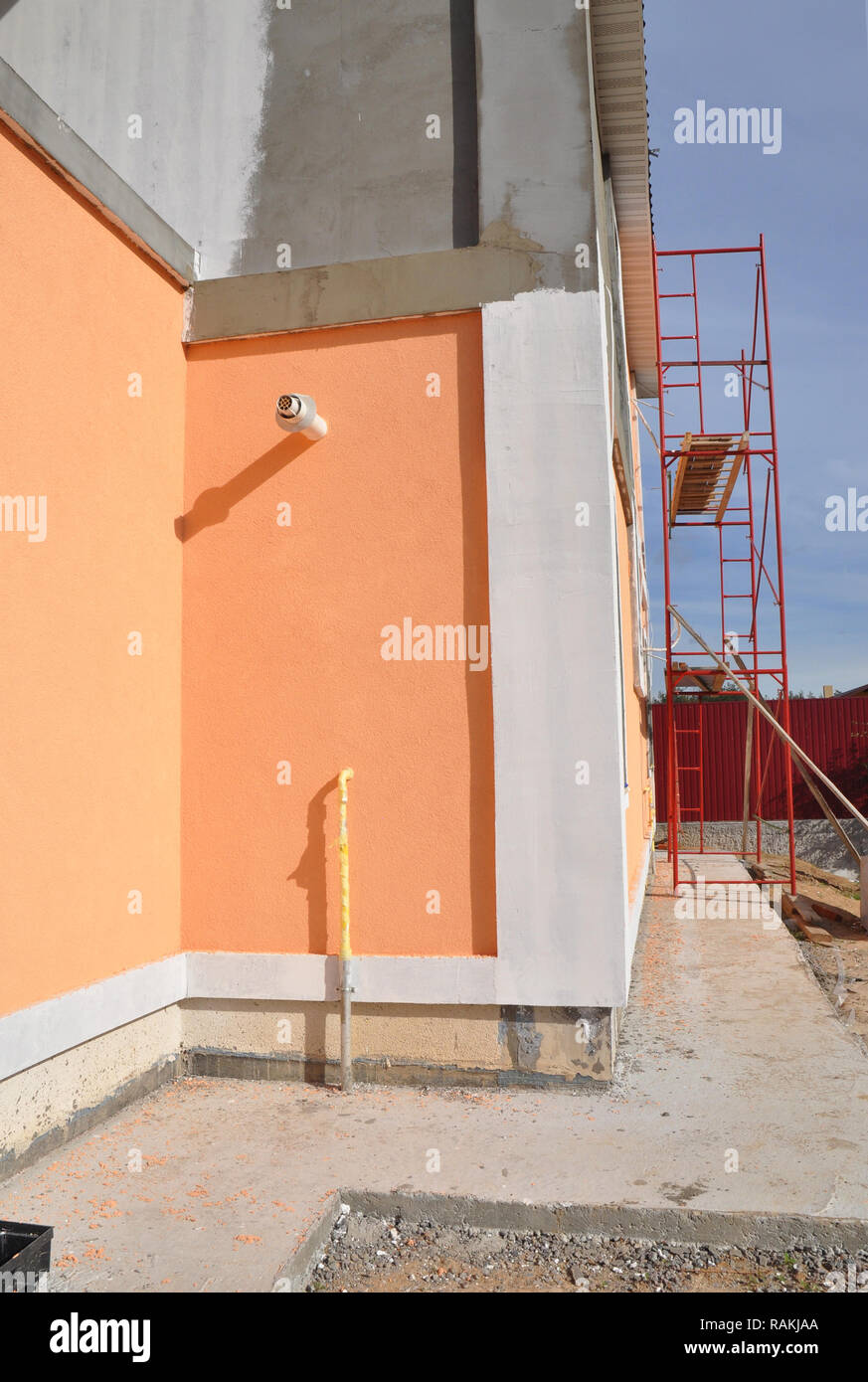 Painting house walls. New house construction foundation waterproofing, damp proofing, insulation with contrete path to avoid water leaks for home wall - Stock Image