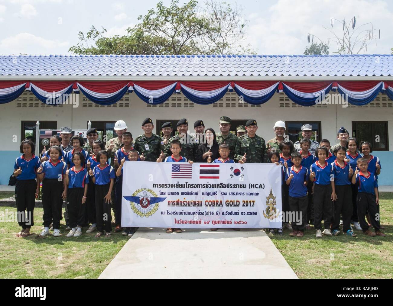 RAYONG PROVINCE, Thailand (Feb. 19, 2017) – Gen. Ponpipat Benyasri, Deputy Chief of Joint Staff, Royal Thai Armed Forces, poses for a group photo with students of Ban Nong Muang School and representatives from U.S. Naval Mobile Construction Battalion 5, Construction and Developmental Regiment, Sattahip Naval Base and Korean Naval Mobile Construction Battalion 2nd Engineer during his visit to thank the Multi-National Forces' joint effort for the school's expansion during Cobra Gold 2017.  Cobra Gold, in its 36th iteration, is the largest Theater Security Cooperation exercise in the Indo-Asia-Pa Stock Photo