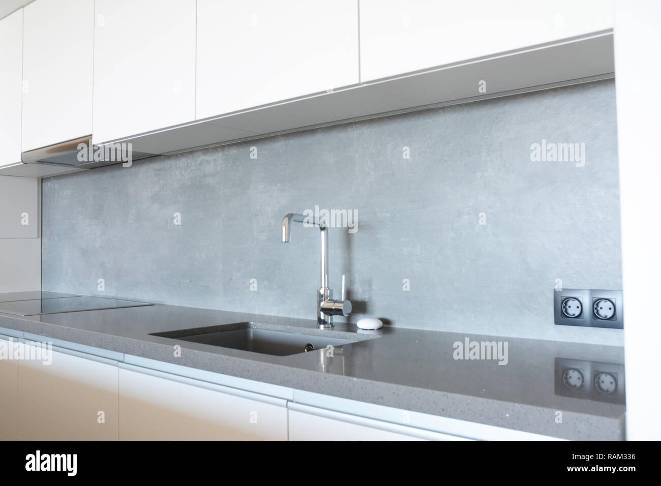 Modern kitchen with metal faucet,  ceramic kitchen sink, kitchen stove, kitchen hood - Stock Image