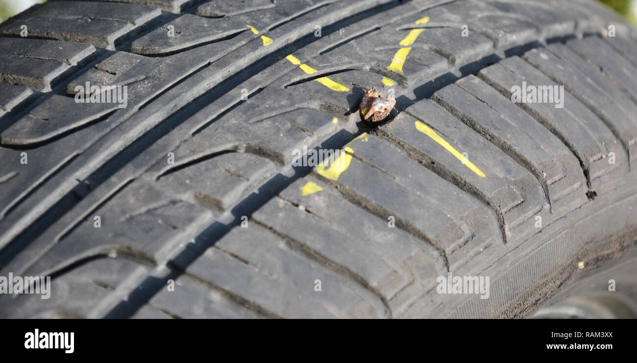 Fix flat car tire.  Car tire damage with nail. - Stock Image