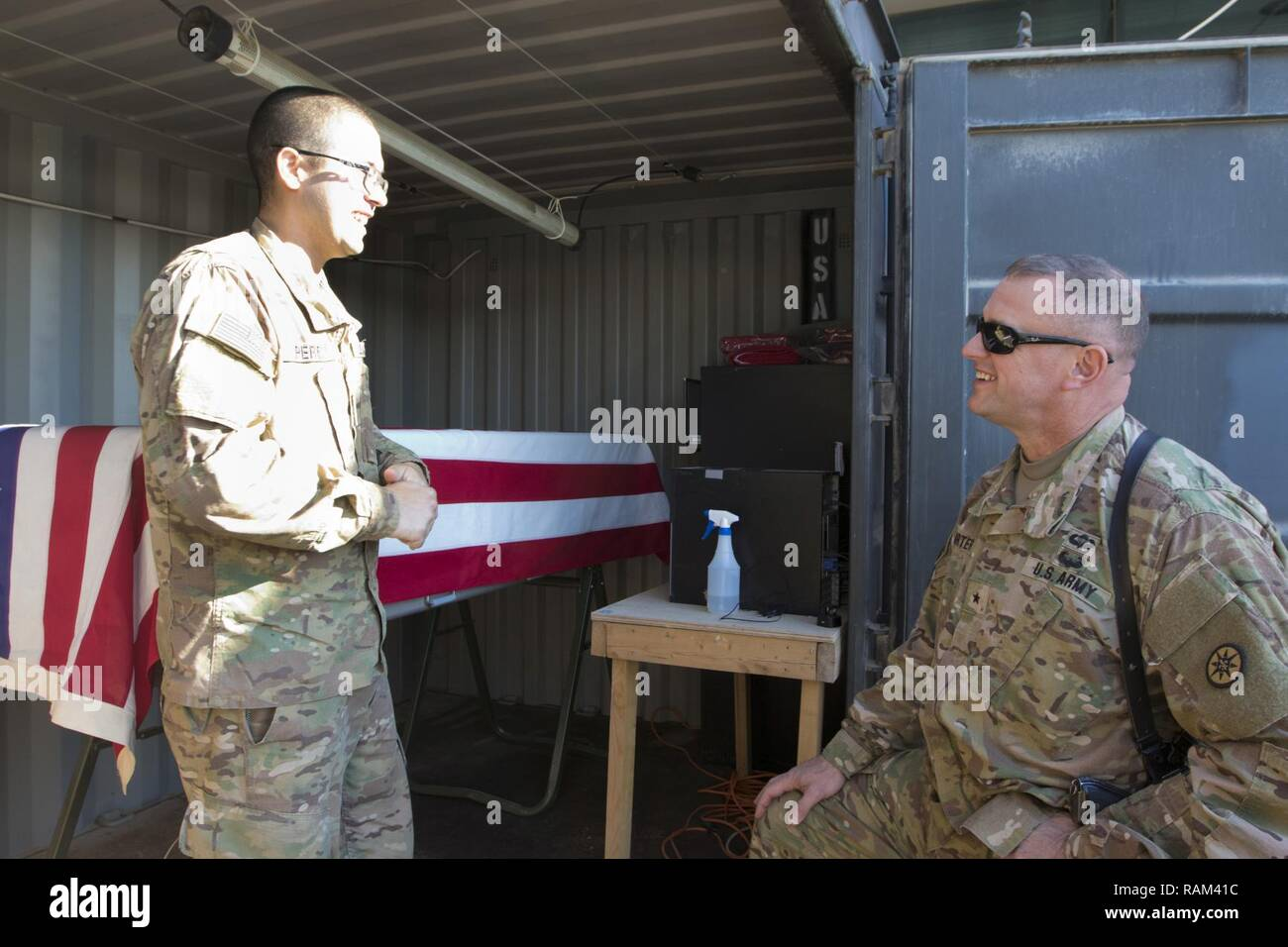 Spc. Jose Perez, a mortuary affairs specialist with the 246th Quartermaster Company (Mortuary Affairs), an U.S. Army Reserve unit based out of Mayaguez, Puerto Rico, (left), explains the capabilities of a Mobile Integrated Remains Collections System (MIRCS) to Brig. Gen. Robert D. Harter, deputy commanding general of the 1st Sustainment Command (Theater) / commanding general of the 316th Sustainment Command (Expeditionary), (right), in Erbil, Iraq on February 3, 2017. - Stock Image