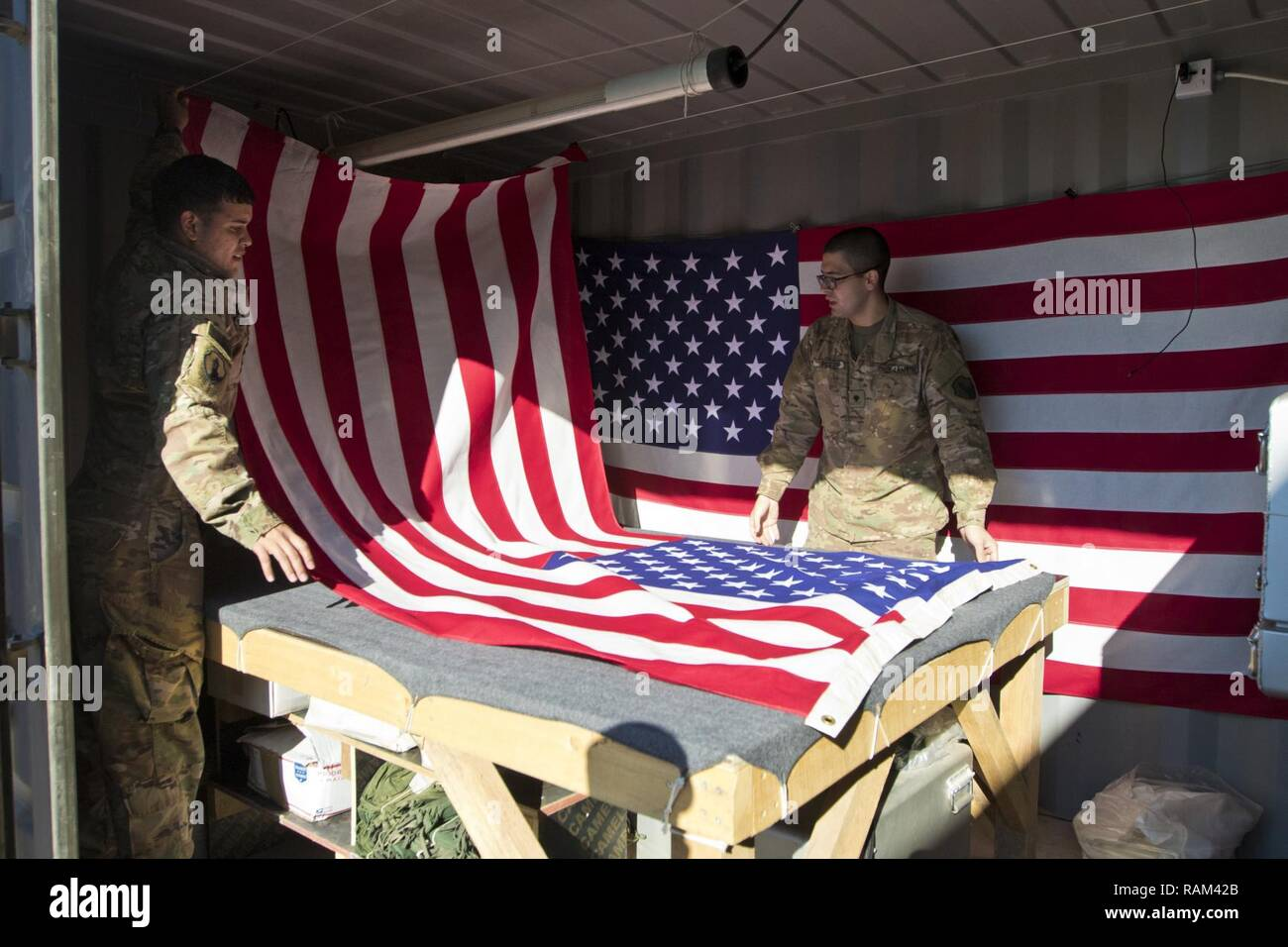 Spc. Brian Ramirez, (left), and Spc. Jose Perez, (right), both mortuary affairs specialists with the 246th Quartermaster Company (Mortuary Affairs), an U.S. Army Reserve unit based out of Mayaguez, Puerto Rico, drapes an American Flag over a transfer case in Erbil, Iraq on February 3, 2017. - Stock Image