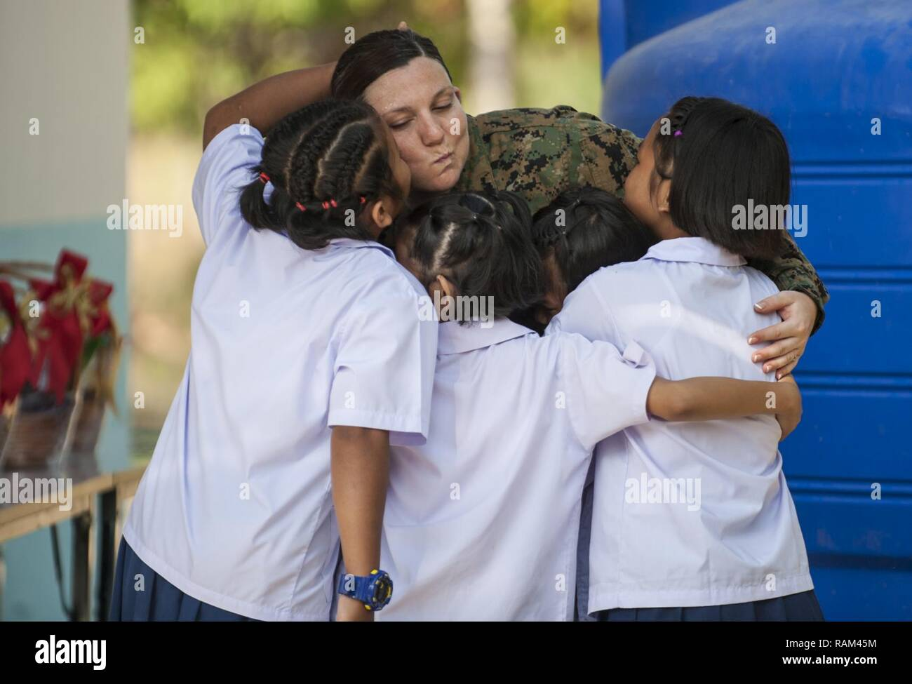 RAYONG PROVINCE, Thailand (Feb. 21, 2017) – Hospital Corpsman 1st Class Samantha Clark, assigned to 1 Marine Expeditionary Force Headquarters Group, bids farewell to Thai students during a dedication ceremony, marking the completion of the Ban Nong Muang school expansion project. The project was a joint effort by the U.S. Naval Mobile Construction Battalion 5, Construction and Developmental Regiment, Sattahip Naval Base and Korean Naval Mobile Construction Battalion 2nd Engineer, part of Cobra Gold 2017. Cobra Gold, in its 36th iteration, is the largest Theater Security Cooperation exercise in Stock Photo