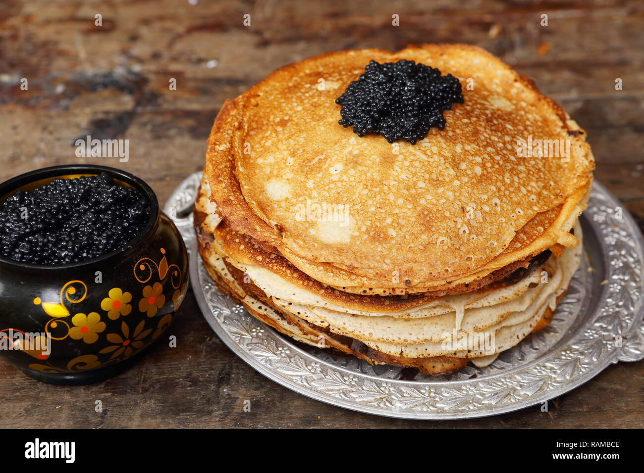 Still life with pancakes and black caviar on a wooden table - Stock Image