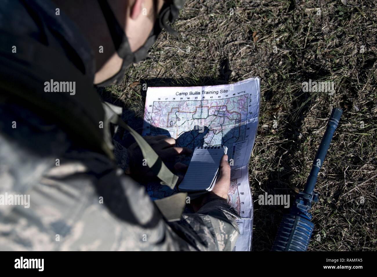 An Air Force Academy Cadet plots location points before conducting land navigation during an Air Liaison Officer Aptitude Assessment, Feb. 15, 2017, at Camp Bullis, Texas. The cadets were ambushed by cadre firing blanks multiple times during the land navigation portion of their assessment. - Stock Image
