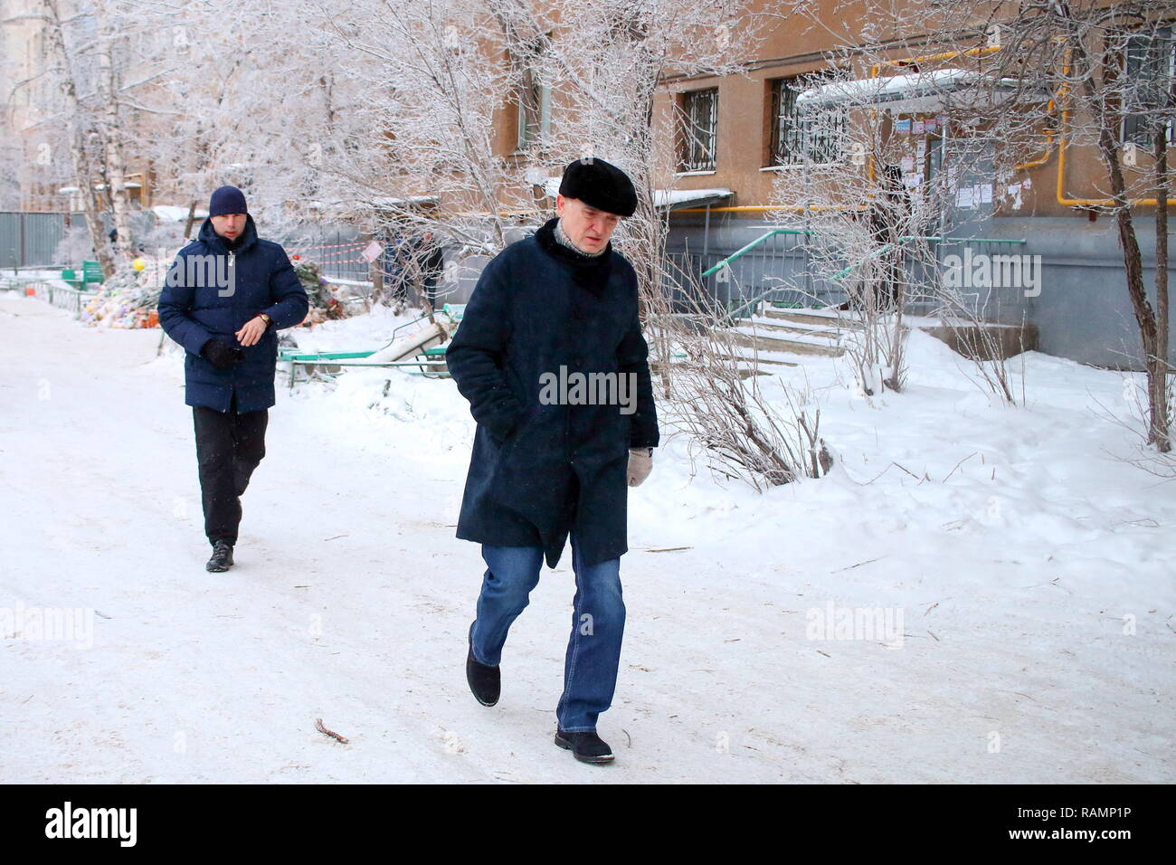 Magnitogorsk, Russia. 04th Jan, 2019. MAGNITOGORSK, RUSSIA - JANUARY 4, 2019: The Governor of Chelyabinsk Region, Boris Dubrovsky (front), outside a partially collapsed building at 164 Karla Marksa Street in the city of Magnitogorsk; a section of the ten-storeyed apartment block collapsed early on 31 December 2018 following a gas explosion; 39 people died in the accident. Valery Sherdyukov/TASS Credit: ITAR-TASS News Agency/Alamy Live News - Stock Image