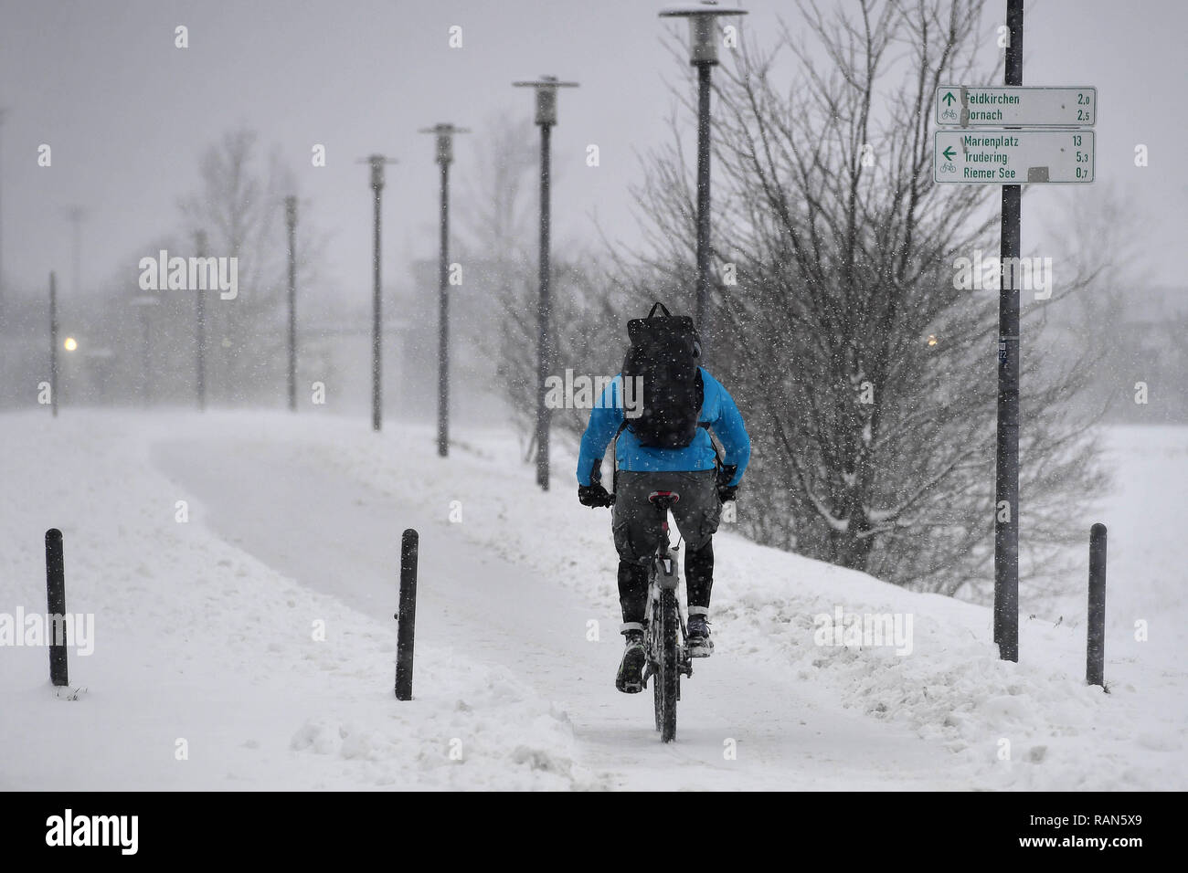 Munich Riem, Deutschland. 05th Jan, 2019. Wetterfeature-Fahrradkurier, Fahrradfahrer with backpack defies the snowdrifts and windbows on a snow-covered path in the Riemer Park.Radfahren in the snow Continuing snowfall on 05.01.2019, ensure snow chaos, traffic chaos, winter in Bavaria.   usage worldwide Credit: dpa/Alamy Live News Credit: dpa picture alliance/Alamy Live News Stock Photo