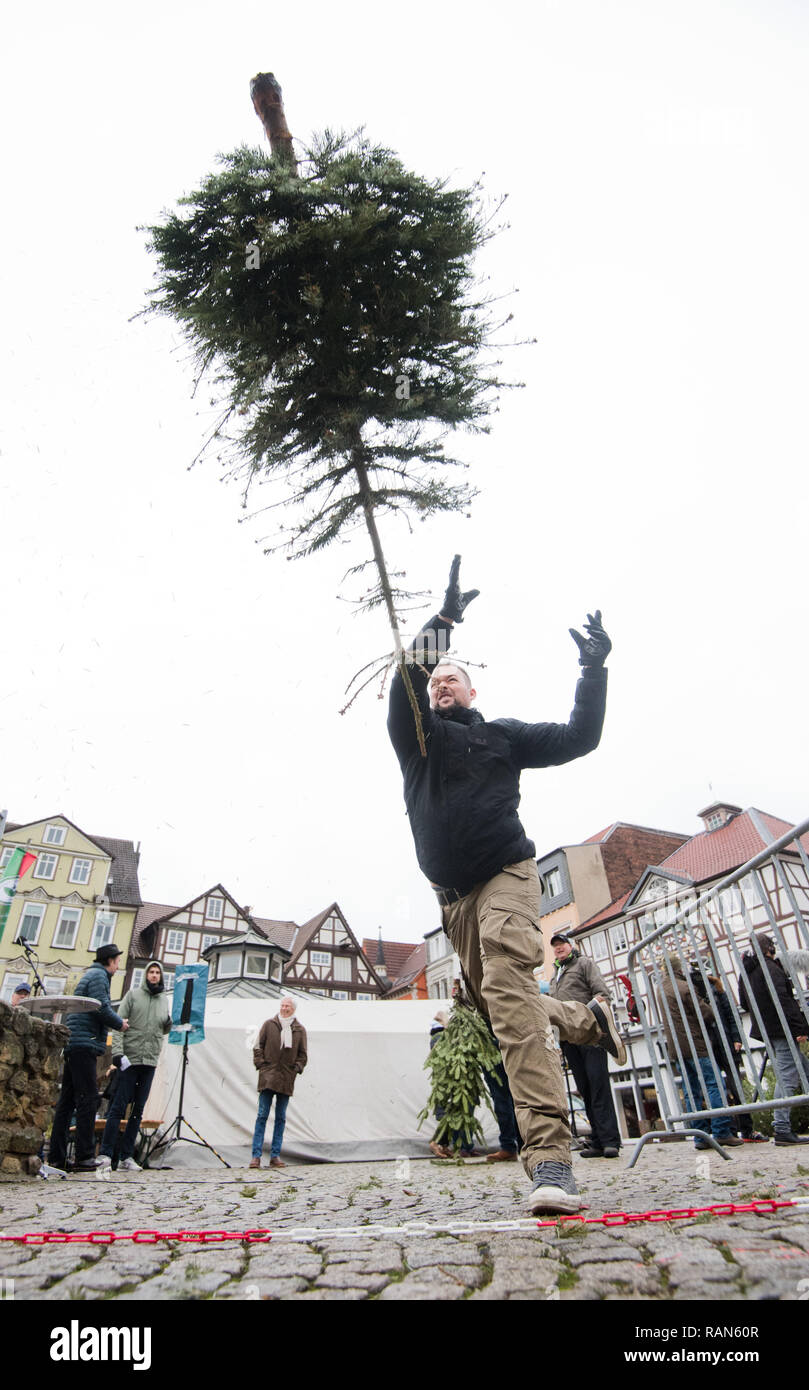 Peine, Germany. 05th Jan, 2019. A participant of the 1st Peiner Tannenbaum-Weitwurf-Wettbewerb throws a fir tree on the market place. For a good cause the Bürger-Jäger-Corps Peine calls for the disposal of old Christmas trees. In the Fir Tree Long Throw Competition, the trees may then be thrown as far as possible. Credit: Julian Stratenschulte/dpa/Alamy Live News - Stock Image