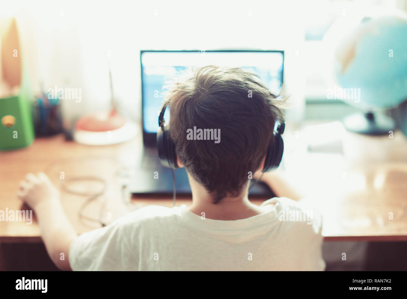 Talented gamer left handed boy playing on laptop indoors - Stock Image