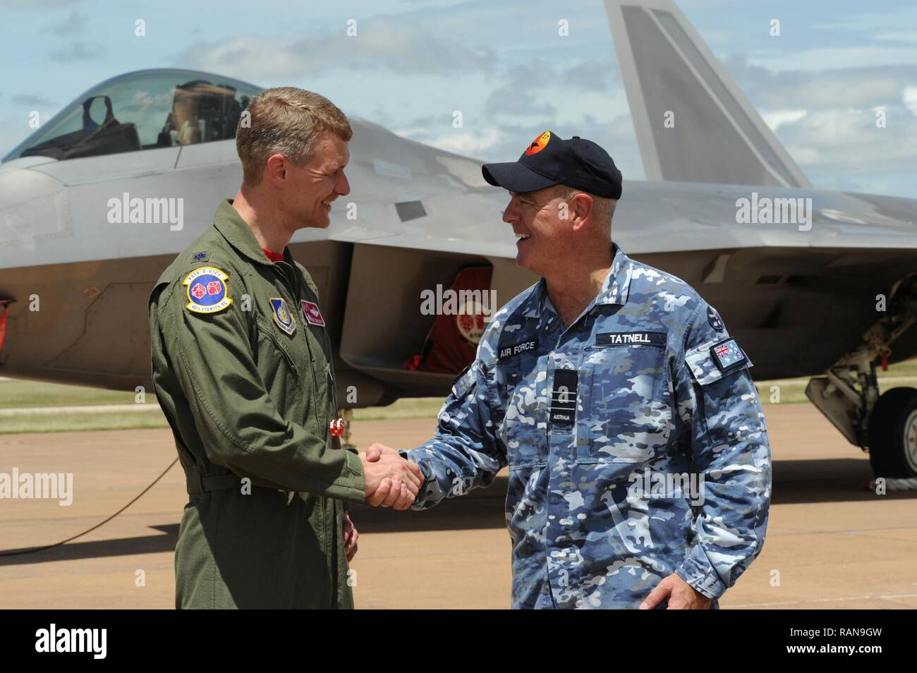 U.S. Air Force Lt. Col. David Skalicky, 90th Fighter Squadron commander, and Wing Commander Andrew Tatnell, Royal Australian Air Force Base Tindal Senior Australian Defence Force Officer, shake hands in front of a U.S. F-22 Raptor at RAAF Base Tindal, Australia, Feb. 24, 2017. Twelve F-22 Raptors and approximately 200 U.S. Air Force Airmen are in Australia as part of the Enhanced Air Cooperation, an initiative under the Force Posture Agreement between the U.S. and Australia. - Stock Image
