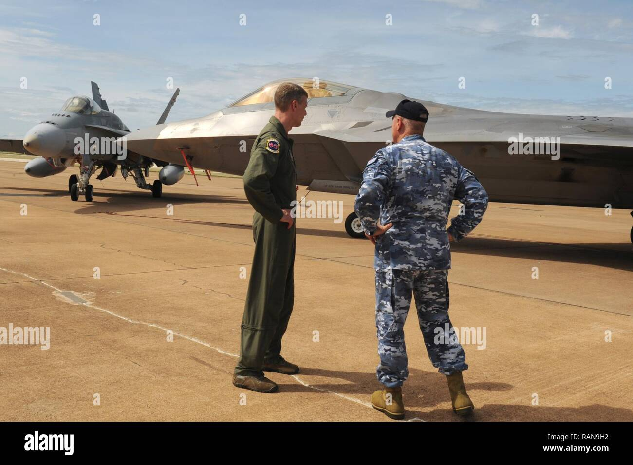 U.S. Air Force Lt. Col. David Skalicky, 90th Fighter Squadron commander, and Wing Commander Andrew Tatnell, Royal Australian Air Force Base Tindal Senior Australian Defence Force Officer, discuss the combined capabilities of the RAAF F/A-18A/B Hornet and U.S. F-22 Raptor at RAAF Base Tindal, Australia, Feb. 24, 2017. Twelve F-22 Raptors and approximately 200 U.S. Air Force Airmen are in Australia as part of the Enhanced Air Cooperation, an initiative under the Force Posture Agreement between the U.S. and Australia. - Stock Image