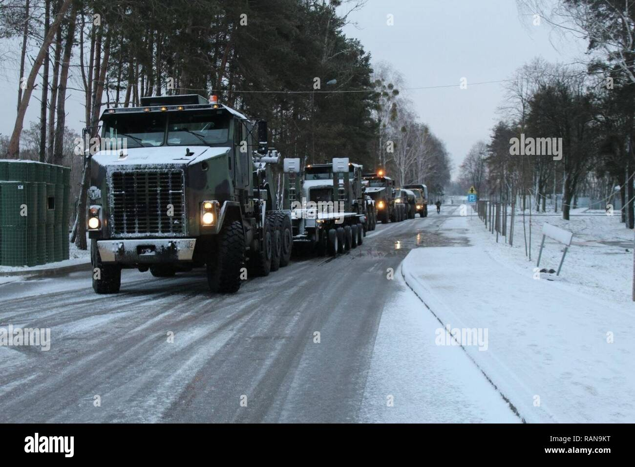 SOCHACZEW, Poland - Soldiers prepare for onward movement after resting overnight, Feb. 21, 2017. A heavy equipment transporter (HET) team, comprised of American and British HETs, verified main supply routes capable of moving an M1A2 Abrams tank across the Suwalki gap, the gateway to the Baltic countries, on a convoy that started Feb. 20 in Germany en route to Estonia. - Stock Image