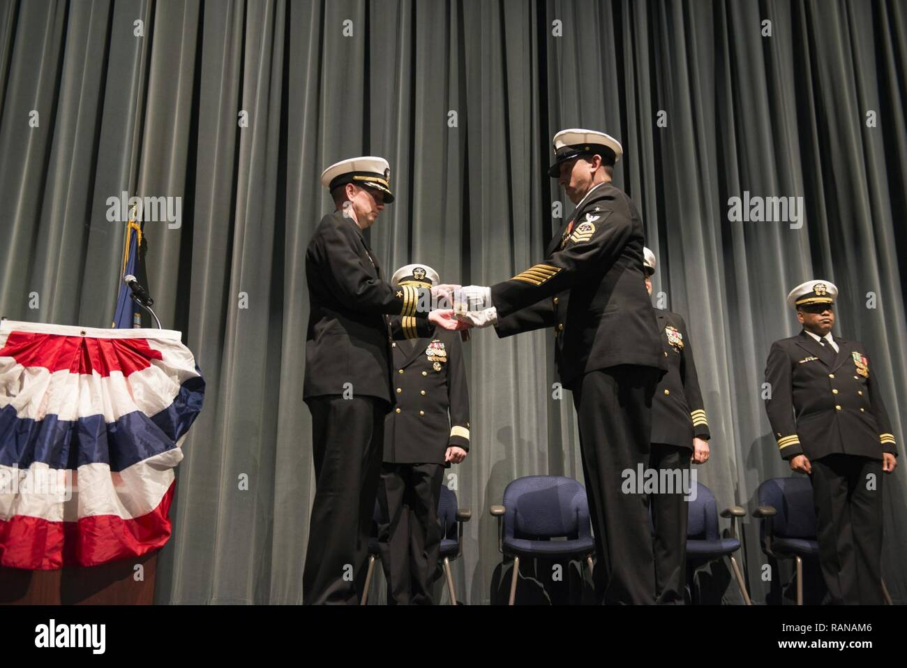 KEYPORT, Wash. (Feb. 27, 2017) Cmdr. Donald Tenney, left, commanding officer of the Los Angeles-class fast-attack submarine USS Albuquerque (SSN 706) is presented with Albuquerque's commissioning pennant by the Chief of the Boat, Senior Chief Sonar Technician Neal Bederson, during a decommissioning ceremony held at Keyport Undersea Museum. Albuquerque was commissioned May 21, 1983 at Naval Base New London in Groton, Connecticut. - Stock Image