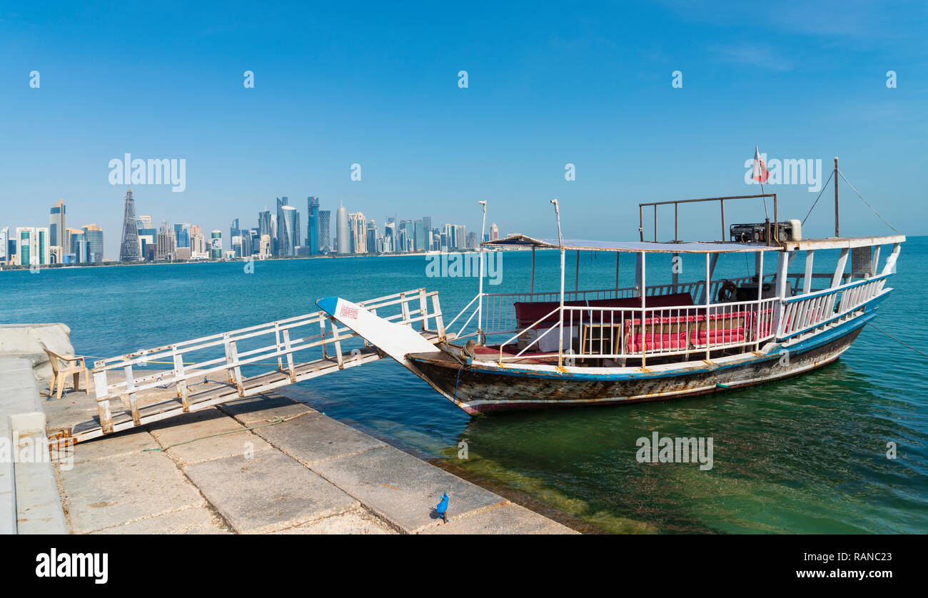 Traditional dhow passenger ferry and view of West Bay business district from The Corniche in Doha, Qatar - Stock Image