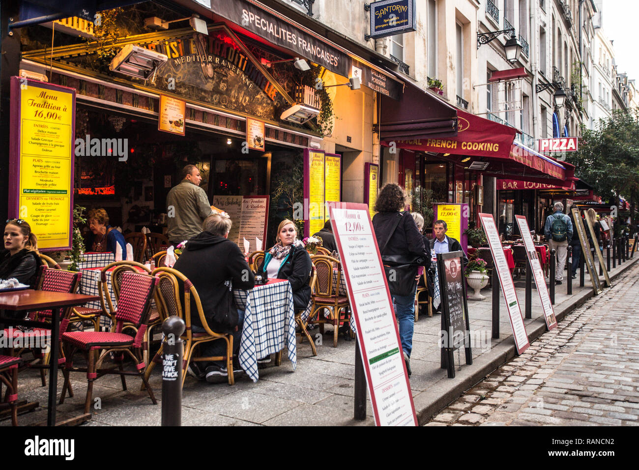 PARIS, FRANCE - OCTOBER 9, 2014: Street scene from the Latin Quarter, Saint-Michel in Paris France with outdoor cafes and people. - Stock Image