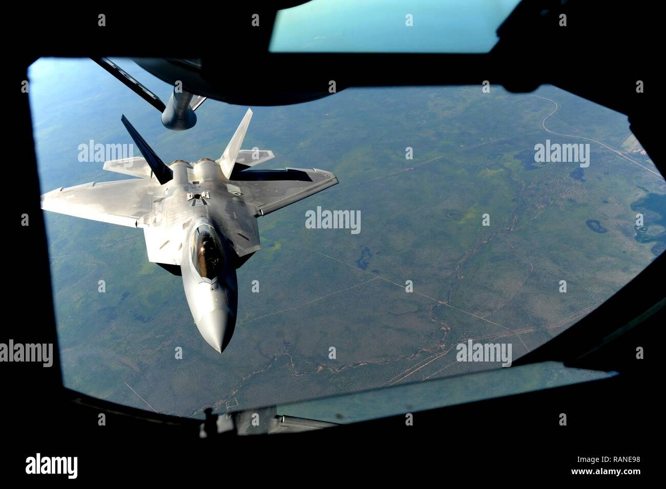 A U.S. Air Force F-22 Raptor assigned to the 90th Fighter Squadron approaches a U.S. Air Force KC-135 Stratotanker in order to receive fuel in the skies above Royal Australian Air Force Base Tindal, Australia, March 2, 2017. Twelve F-22 Raptors and approximately 200 U.S. Air Force Airmen participated in the first Enhanced Air Cooperation, an initiative under the Force Posture Agreement between the U.S. and Australia. - Stock Image