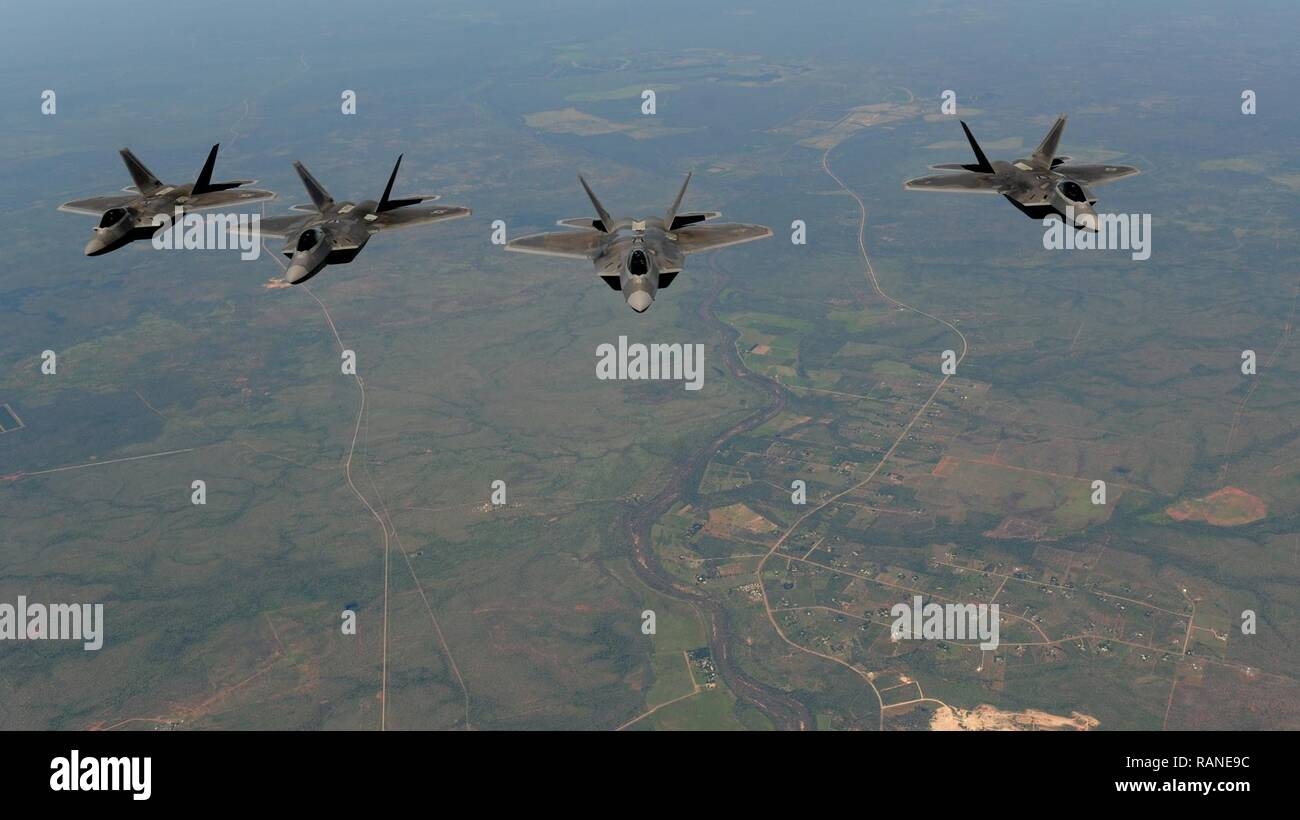 Four U.S. Air Force F-22 Raptors assigned to the 90th Fighter Squadron fly in formation in the skies above Royal Australian Air Force Base Tindal, Australia, March 2, 2017. Twelve F-22 Raptors and approximately 200 U.S. Air Force Airmen participated in the first Enhanced Air Cooperation, an initiative under the Force Posture Agreement between the U.S. and Australia. - Stock Image