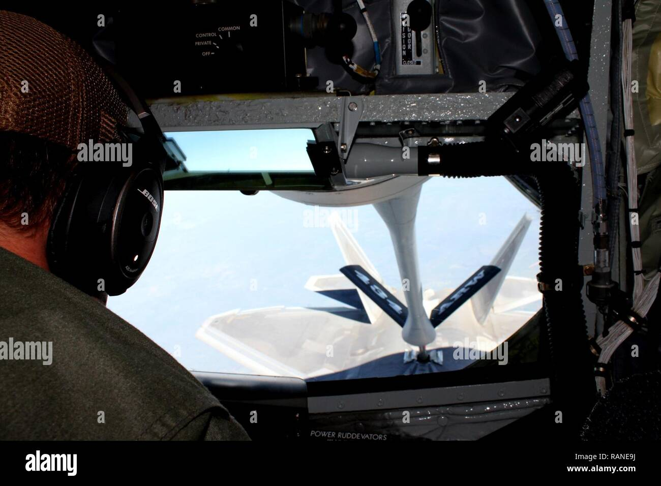 U.S. Air Force Master Sgt. Joshua Welch, 434th Air Refueling Wing boom operator, guides a U.S. Air Force KC-135 Stratotanker boom in place in order to refuel a U.S. Air Force F-22 Raptor above Royal Australian Air Force Base Tindal, Australia, March 2, 2017. Twelve F-22's and approximately 200 U.S. Air Force Airmen participated in the first Enhanced Air Cooperation, an initiative under the Force Posture Agreement between the U.S. and Australia. - Stock Image