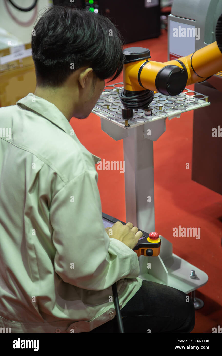 Worker control robot arm to loading and unloading workpiece - Stock Image