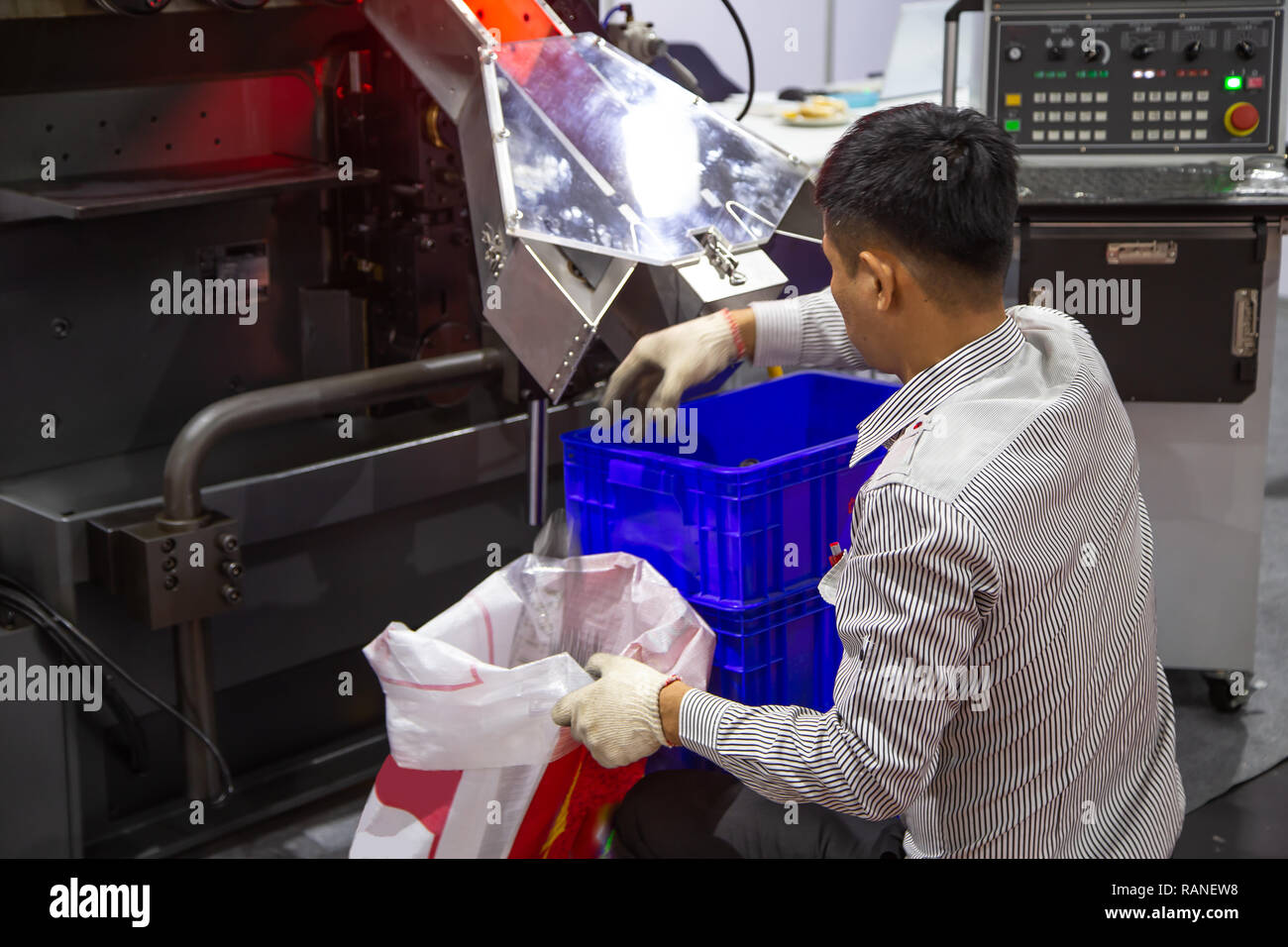 Worker collect spring products in busket from spring coiling machine - Stock Image